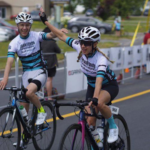 Une femme à bicycle lève le bras au Granfondo