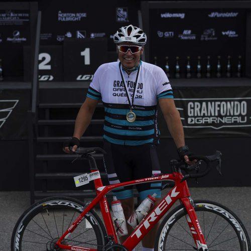 Un homme au Granfondo avec un bicycle rouge et une médaille