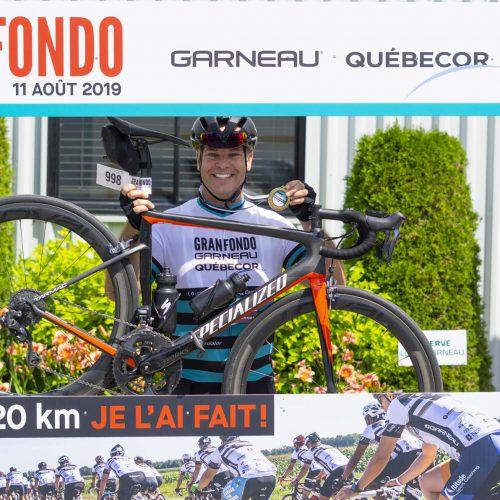 Un homme montre sa médaille et son bicycle au Granfondo